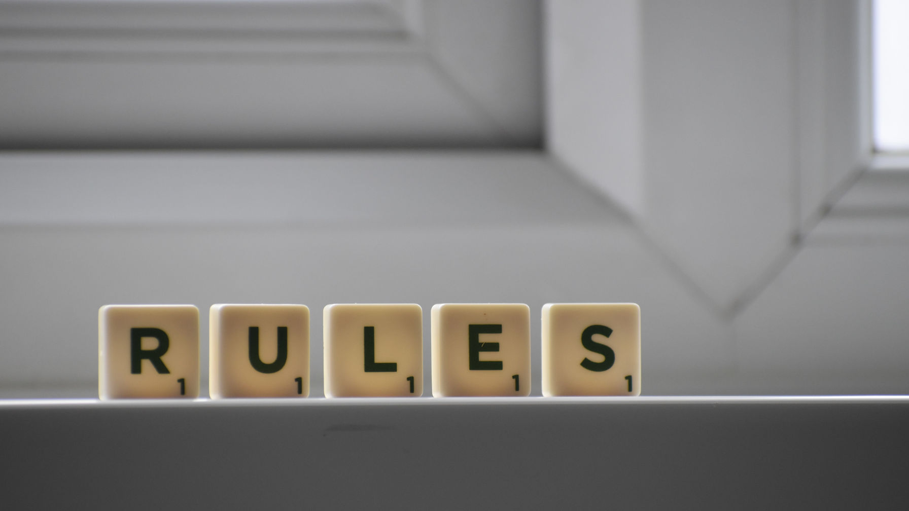Decorative image that uses letters from the game of Scrabble to spell out 'RULES'.