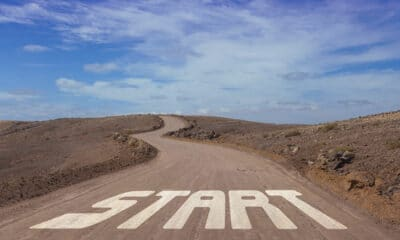 """Winding dirt road that goals uphill in a desert area.  At the beginning, """"START"""" is painted on the roadway."""